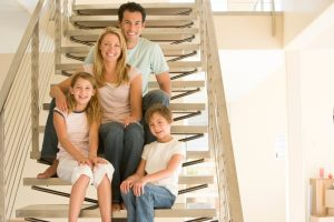 Family of 4 sitting on staircase inside their home