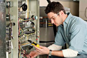 Technician wire testing HVAC unit