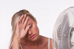 Young blonde woman holding her hand over her forehead in front of a fan